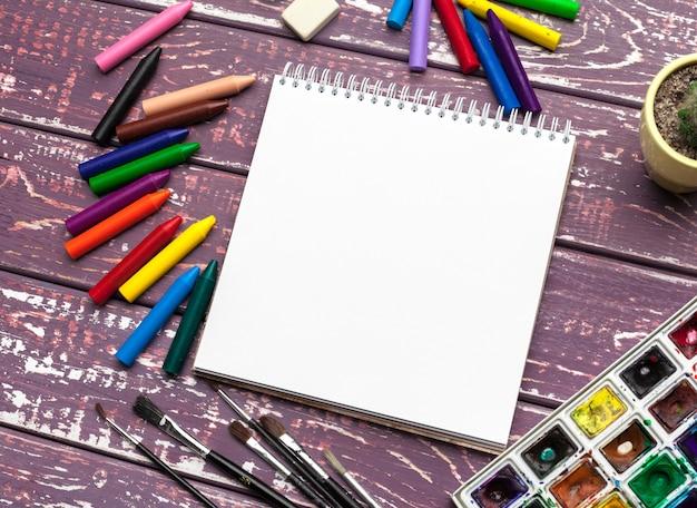 Vernici dell'acquerello e blocco note in bianco sullo scrittorio di legno