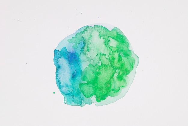 Vernici verdi e acquamarina a forma di cerchio su carta bianca