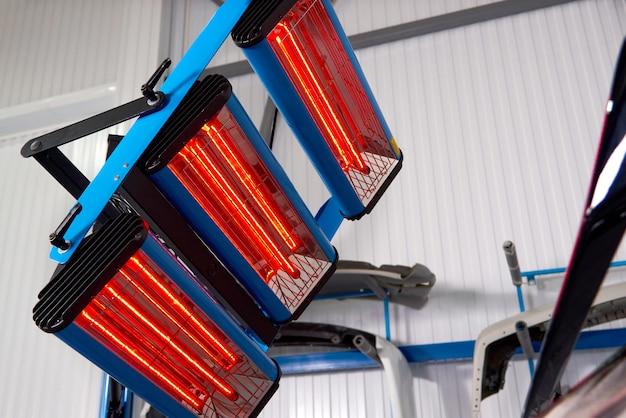 Verniciatura e asciugatura sotto le lampade in una scatola professionale di parti di carrozzeria dopo l'applicazione di stucco e vernice sul paraurti
