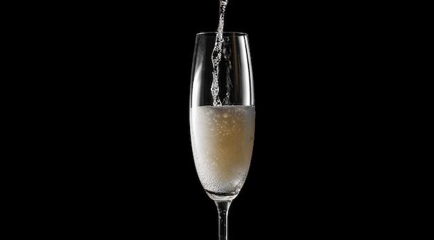 Versa lo champagne in un bicchiere vuoto. su uno sfondo nero