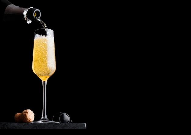 Versando champagne giallo dalla bottiglia al bicchiere con sughero e gabbia metallica sul bordo di marmo nero