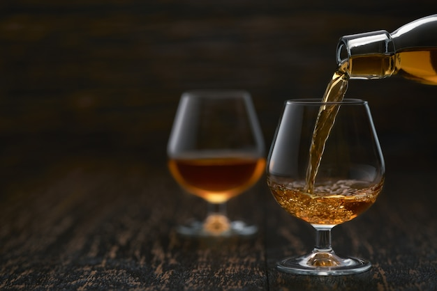 Versando il cognac dalla bottiglia nel bicchiere contro il tavolo di legno.