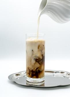 Versando il latte in un bicchiere di caffè