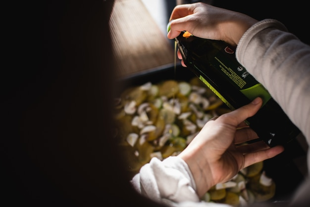 Versando l'olio d'oliva sulle verdure