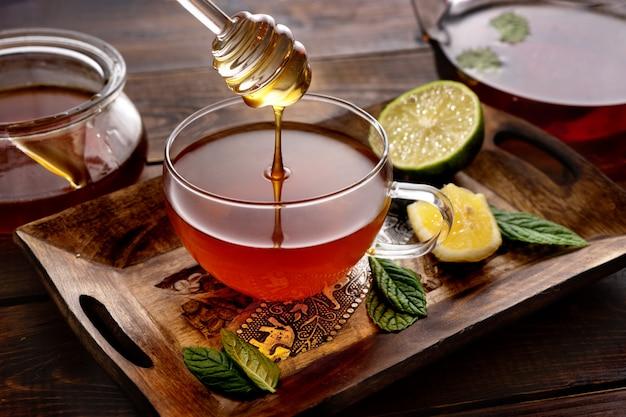 Versando un miele nella tazza di tè sulla tavolozza di legno in stile rustico