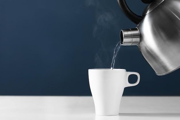 Versare acqua calda in una tazza su uno sfondo scuro