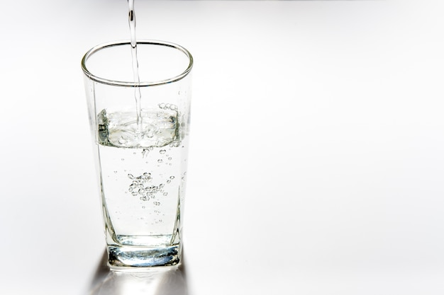 Versare acqua potabile nel bicchiere alto
