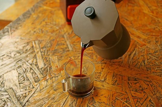 Versare il caffè espresso appena preparato dalla caffettiera moka