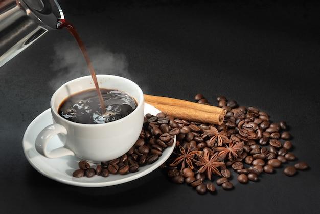 Versare il caffè nella tazza di caffè con anice, cannella e chicchi di caffè sulla scrivania nera