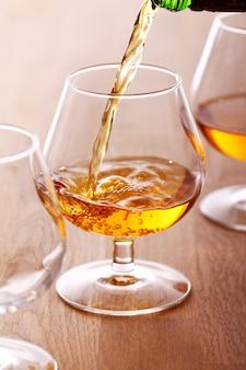 Versare il cognac nel bicchiere