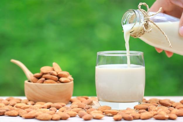 Versare il latte di mandorle puro dalla bottiglia di vetro con mandorle in una ciotola