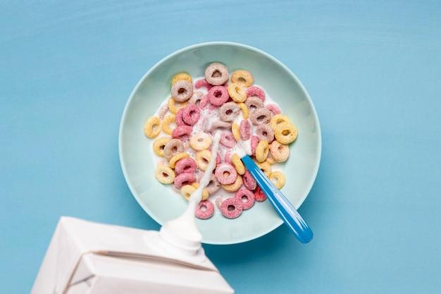 Versare il latte fresco cremoso in una ciotola piena di cereali