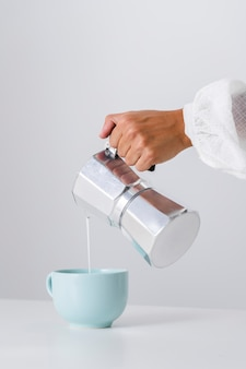 Versare il latte in una tazza di ceramica