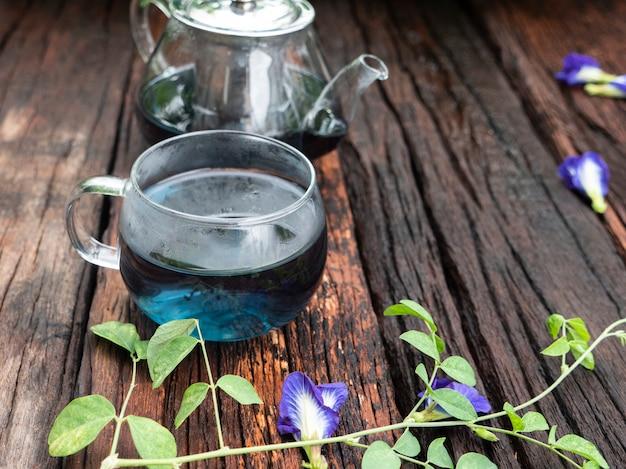 Versare il tè caldo in un bicchiere con tè di fiori di pisello.
