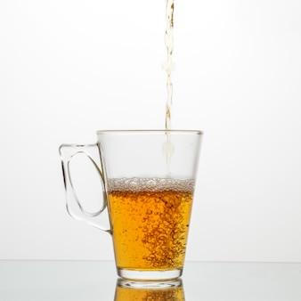 Versare il tè in una tazza di vetro.