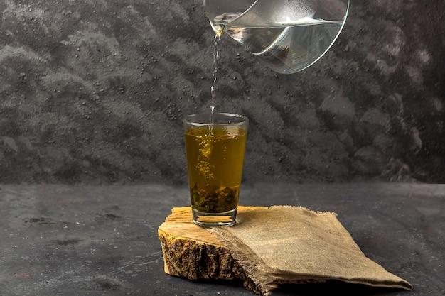 Versare il tè verde con acqua bollente da una teiera di vetro trasparente. tè antiossidante e tossinico in un bicchiere dopo la spa