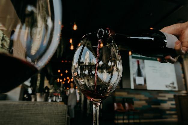 Versare il vino rosso dalla bottiglia nel bicchiere da vino