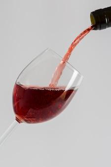 Versare il vino rosso dalla bottiglia nel bicchiere