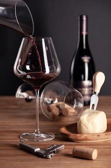 Versare il vino rosso in un bicchiere di cristallo