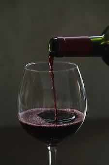 Versare il vino rosso in vetro