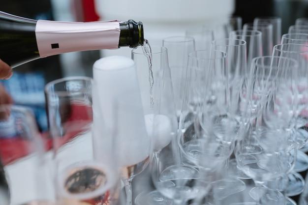 Versare il vino spumante dalla bottiglia nel bicchiere di champagne