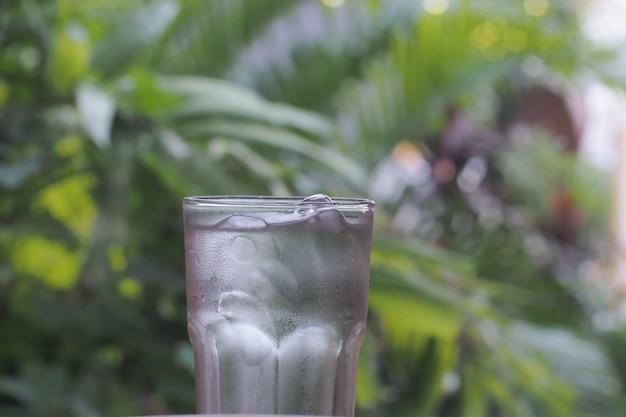Versare l'acqua in un bicchiere contro lo sfondo della natura
