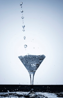 Versare l'acqua in un primo piano di vetro trasparente