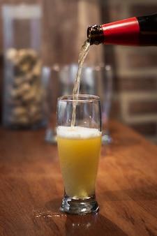 Versare la birra dalla bottiglia al processo di pinta
