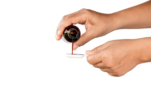 Versare la medicina nel cucchiaio per nutrire il bambino malato