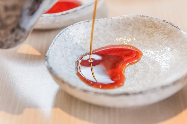 Versare la salsa di soia nella ciotola