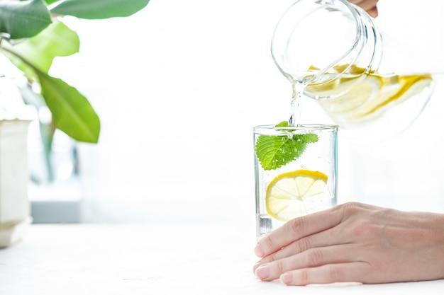 Versare un bicchiere d'acqua con limone, ghiaccio e menta su un tavolo bianco