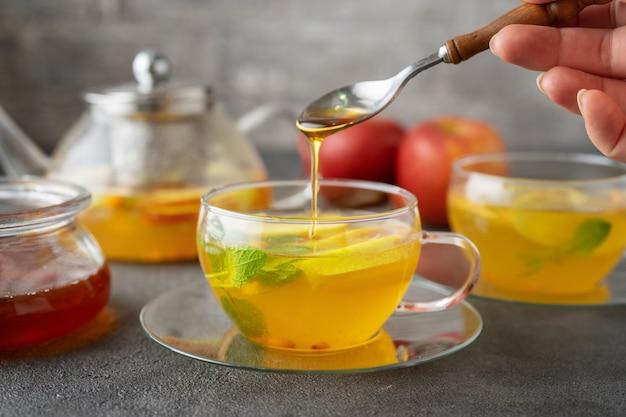 Versare un miele in una tazza di vetro di tè alla frutta