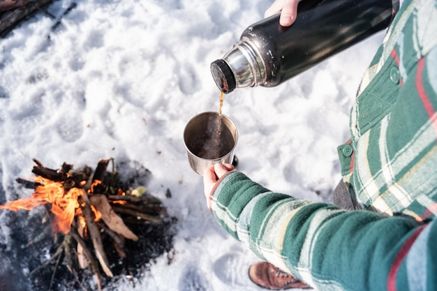Versare una bevanda calda dal thermos in un campeggio. persona che si scalda vicino a un falò, colpo di punto di vista