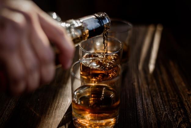 Versare una forte bevanda alcolica nei bicchieri che si trovano sul tavolo di legno