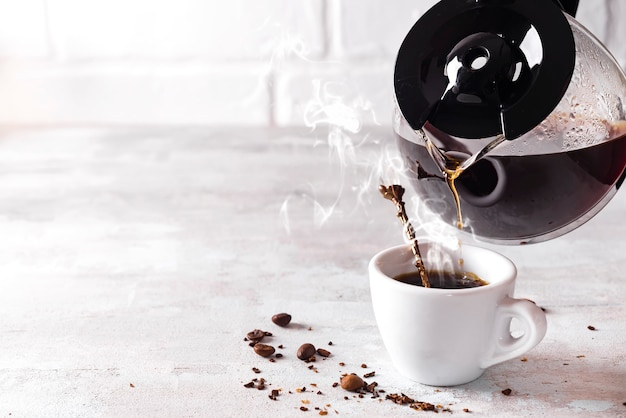 Versare una tazza di caffè caldo nel bicchiere per la colazione.