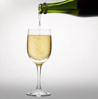 Versare vino bianco frizzante in un bicchiere da vino