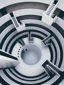 Verticale di alto angolo di un interno in bianco e nero con molte scale