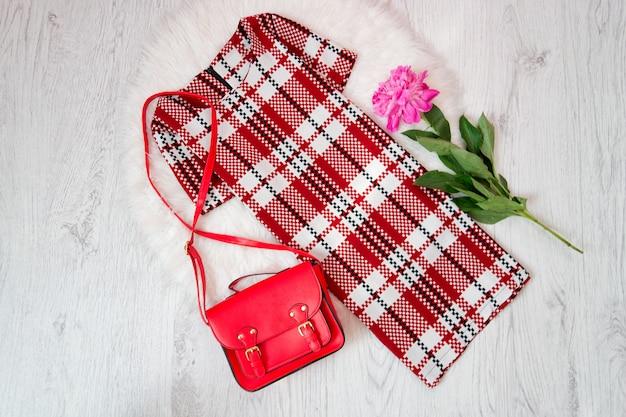 Vesti in una gabbia una borsa bianca-rossa e rossa, peonie su pelliccia bianca. concetto alla moda