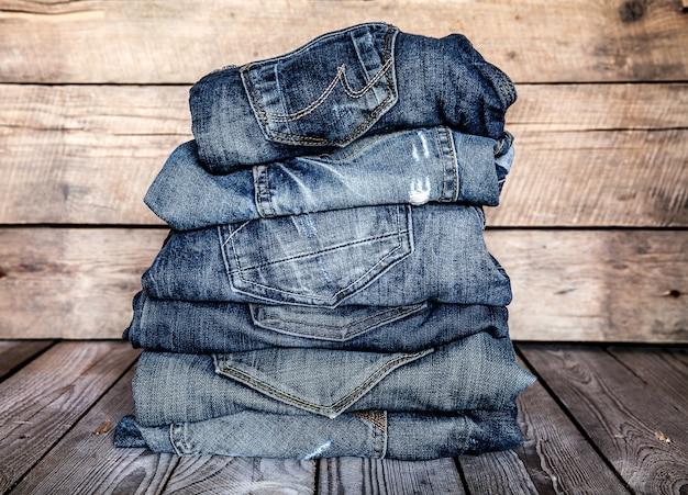 Vestiti alla moda. mucchio di jeans su un tavolo di legno