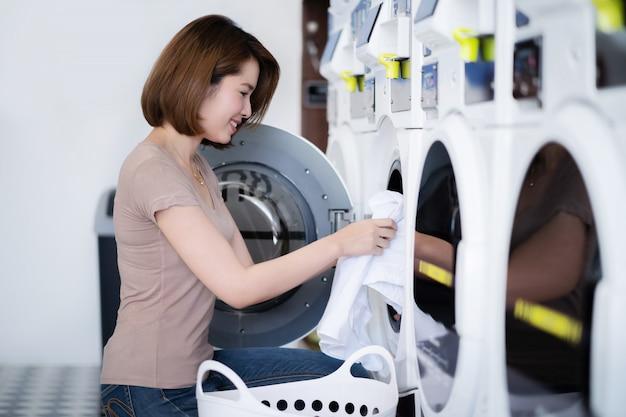 Vestiti asiatici di lavaggio della donna alla lavanderia