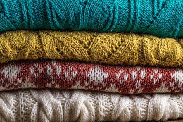 Vestiti caldi, a maglia, invernali su uno sfondo di legno. brutto maglione di natale