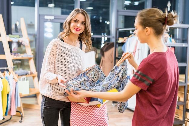 Vestiti d'acquisto attraenti della giovane donna nel negozio di abbigliamento