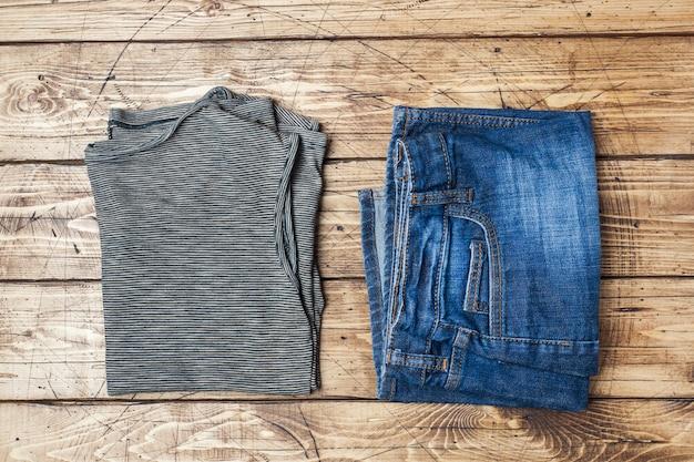 Vestiti da donna estiva. foto di moda piatta laica. maglietta a strisce grigia e blue jeans su fondo di legno.