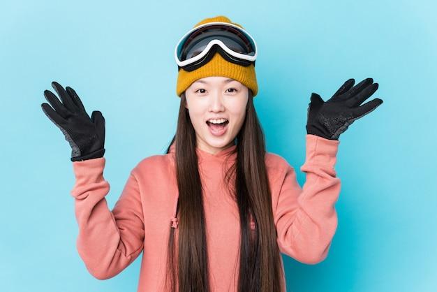Vestiti da sci da portare della giovane donna cinese isolati ricevendo una piacevole sorpresa, eccitati e alzando le mani.