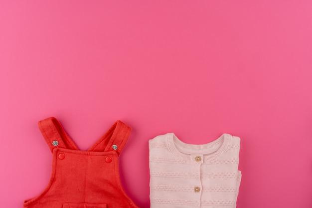 Vestiti del bambino su sfondo rosa vista dall'alto