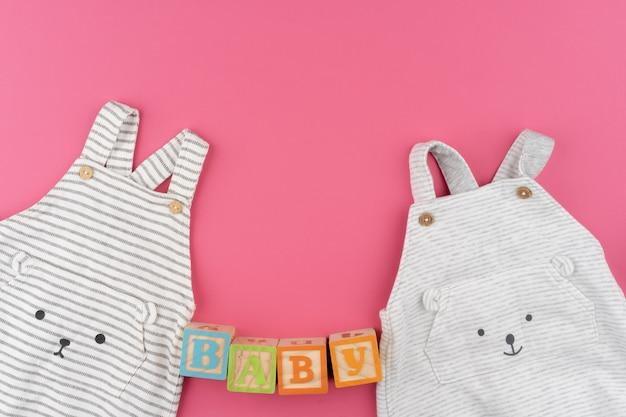 Vestiti del bambino sulla superficie rosa