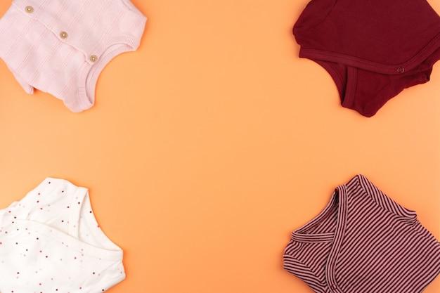 Vestiti della neonata sulla vista superiore arancio