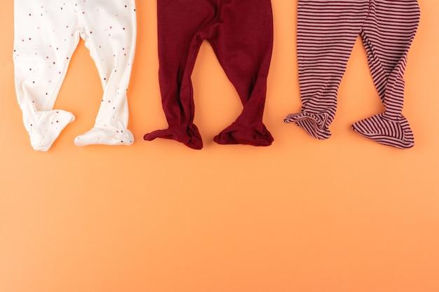 Vestiti della neonata sulla vista superiore del fondo arancio