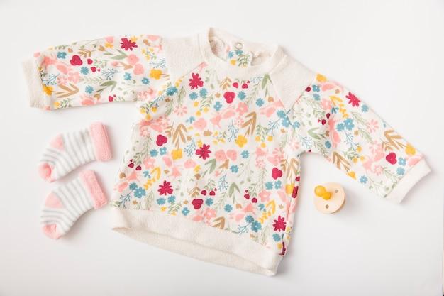 Vestiti e calzini del bambino con la tettarella isolata su fondo bianco