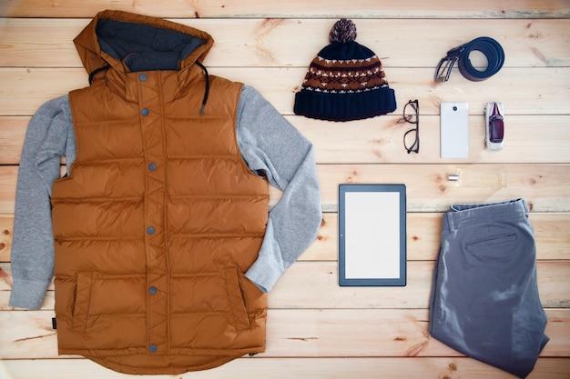 Vestiti ed accessori degli uomini su un fondo di legno.